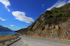 Mountain road beside lake with blue sky Royalty Free Stock Image