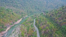 Mountain road meanders along rocky river in tropical highland. Mountain road with moving car meanders along long rocky river streaming among tropical jungle in stock footage