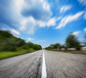 Mountain road in motion blur effect. Asphalt highway Royalty Free Stock Images