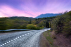 Mountain road with motion blur effect at dusk. Asphalt highway.  Stock Image