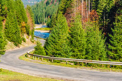 Mountain road near river in autumn forest. Empty winding asphalt road near the mountain river in autumn forest Stock Image