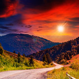 Mountain Road Near The Coniferous Forest With Cloudy Sunset Sky Royalty Free Stock Photos
