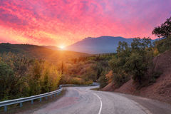 Mountain road passing through the forest with dramatic colorful sky and red clouds at colorful sunset in summer. Mountain Royalty Free Stock Photo