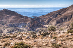 Mountain road passing rugged rocky cliffs. Mountain road winding past rugged rocky cliffs forming a mountain summit against a hot sunny blue sky stock photo