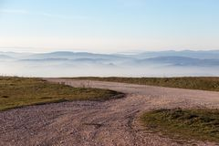 A mountain road pointing toward some distant mountains and hills Royalty Free Stock Photo
