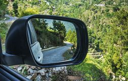A mountain road reflected in a car mirror Royalty Free Stock Photo