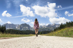 Young woman walking to the mountains. Mountain road to freedom - Young girl freely walking to the beautiful mountain landscape Stock Images