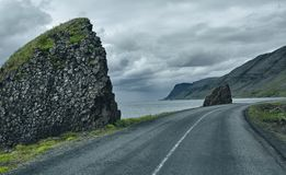 A mountain road to the town of Isafjordur and a view of the fjord. Travel to Iceland. A road along the sea with fog to the town of Isafjordur and a view of the Royalty Free Stock Photos
