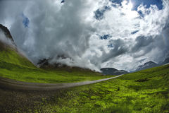 A mountain road to the town of Isafjordur and a view of the fjord. Travel to Iceland. A mountain road with fog and clouds to the town of Isafjordur and a view of Royalty Free Stock Photos