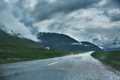 A mountain road to the town of Isafjordur and a view of the fjord. Travel to Iceland. A mountain road with fog to the town of Isafjordur and a view of the fjord Stock Image