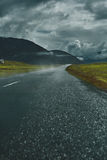 A mountain road to the town of Isafjordur and a view of the fjord. Travel to Iceland. A mountain road with fog to the town of Isafjordur and a view of the fjord Royalty Free Stock Image