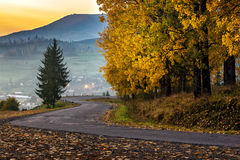 Mountain road to village in mountains. Curve old asphalt road goes through the fog to village in mountains near the forest Royalty Free Stock Images