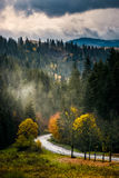 Mountain road to village in mountains. Old asphalt road winding through the fog to village in mountains. forest with yellow foliage in morning light at sunrise Stock Photo