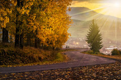 Mountain road to village in mountains at sunset. Curve old asphalt road goes through the fog to village in mountains near the forest in evening light Stock Image