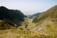 Mountain road through Transfagarasan valley. Transfagarasan mountain road going down through the Goat Valley in Fagaras mountains, Romania. Near the horizon you stock images
