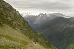 Mountain road and tunnel in italian alps. With high peak glacier scenery in background Stock Photography