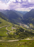 Mountain road and village valley italian alps. Mountain road and valley village  in italian alps with peaks in clouds in background Royalty Free Stock Images