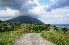 Mountain Road. The winding road atop the rolling landscape seemingly leads to the mountain beyond Royalty Free Stock Image