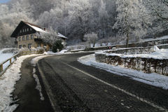 Mountain road in winter. Scenic view of road on forested mountainside in winter with chalet home in background, Liechtenstein Stock Images