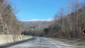 Mountain road in winter. Beautiful, snow-covered mountain tops and bare, white birch trees as seen from the highway in North Carolina in January Stock Image