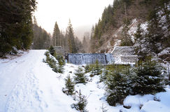 A mountain road on winter season with a small waterfall with a lot of fir trees. Mountain road on winter season with a small waterfall, trees and a river Royalty Free Stock Images