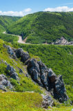 Mountain road. This is an wonderful picture of a rocky mountain with a highway twisting through it that was taken on the Cabot Trail. The day is bright and sunny Royalty Free Stock Photography