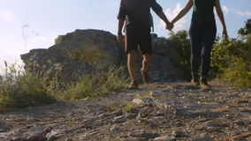 Mountain road. Young couple walking with the top of the mountain at the camera stock video footage
