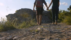 Mountain road. Young couple walking up the mountain.  stock footage