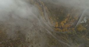 Mountain roads with a lot of mist. Backwards fly over mountain roads with a lot of mist stock footage