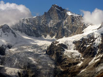 Mountain rocky peak above glacier. Blue sky and white clouds in backround Stock Photo