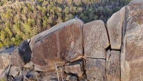 Mountain runner trains on a mountain ridge. Aerial shot of a man running climbs a high rock. 4K stock video footage