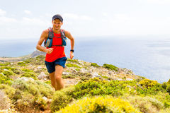 Mountain running man in inspirational landscape. Trail running man, happy cross country runner in inspirational mountains landscape on beautiful day. Training stock image