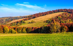 Mountain rural area in late autumn. Season. agricultural field on a hill near the forest with red foliage. beautiful and vivid countryside landscape Royalty Free Stock Photography