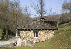 Mountain rural house with stone roof and firewood, Bulgaria Royalty Free Stock Photography