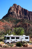 Mountain RV. A motorhome parked at the foot of majestic mountains Stock Photography