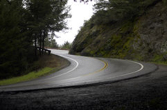 Mountain S bend after rain. A steep corner on a wet winding road Royalty Free Stock Images