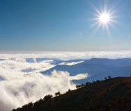 Mountain's scene with sun over clouds Royalty Free Stock Images