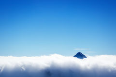 Mountain's top over clouds Stock Images