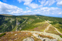 Mountain saddle with footpaths and white clouds in the blue sky Royalty Free Stock Photography