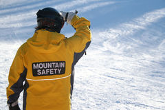 Mountain Safety. A worker at a ski hill ensures the safety of its winter visitors Stock Images