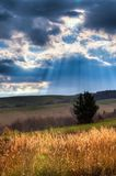 mountain scenery. Sun rays coming out of clouds in beautiful mountain scenery Stock Photo
