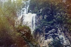 Mountain scenic unspoiled waterfall with ice water flowing over. Rocks and stones Royalty Free Stock Image