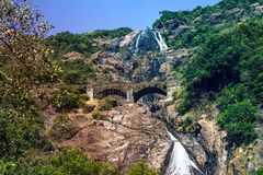 Mountain scenic waterfall and bridge with the railway passing at. Height on a background of green stock photo