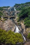 Mountain scenic waterfall and bridge with the railway passing at. Height on a background of green stock images