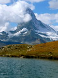 Mountain with sea. Mountain Matterhorn with clouds and lake in the front Stock Images