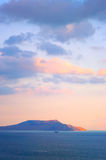 Mountain in sea at sunset Stock Photo