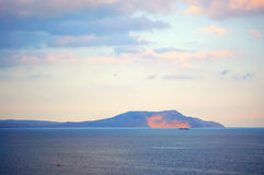 Mountain in sea at sunset Royalty Free Stock Photos