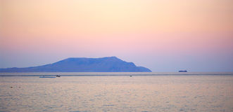 Mountain in sea at sunset Royalty Free Stock Photography