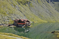 Mountain chalet  on the greenwater lake  Royalty Free Stock Photos