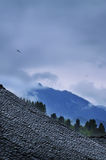 Mountain shelter with fog. A ancient village, a thin mist rising from the mountain in the distance, Birds fly in the sky Stock Photography